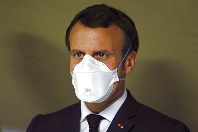 In this Wednesday, March 25, 2020 photo, French President Emmanuel Macron wears a face masks during a visit at the military field hospital in Mulhouse, eastern France. French President Emmanuel Macron acknowledged mistakes Friday in reforming the national hospital system, which has faced years of cost cuts and whose once-renowned facilities have struggled to treat tens of thousands of virus patients. (Mathieu Cugnot/Pool via AP)