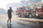 Justin Babcock walks on the street outside of his home in the Pacific Palisades area of Los Angeles as a wildfire burns in the area Monday, Oct. 21, 2019. A furious firefighting air and ground attack beat back the wildfire as it raced up canyon walls toward multimillion-dollar ocean-view homes as some residents evacuated and others stayed behind to try and protect their homes. (AP Photo/Christian Monterrosa)