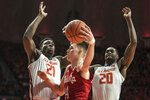 Nebraska's Thorir Thorbjarnarson (34) passes the ball around Illinois' Kofi Cockburn (21) and DaMonte Williams (20) in the second half of a NCAA college basketball game Monday, Feb. 24, 2020, in Champaign, Ill. (AP Photo/Holly Hart)