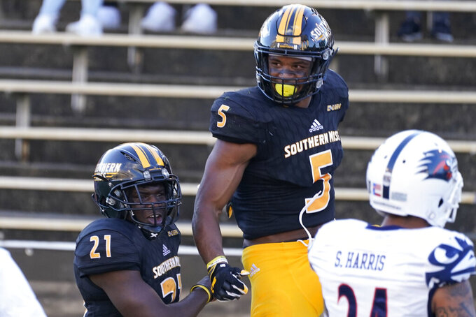 Southern Mississippi wide receiver Tim Jones (5) is boosted by running back Frank Gore Jr. (21) after catching a touchdown pass against UTSA during the first half of an NCAA college football game, Saturday, Nov. 21, 2020, in Hattiesburg, Miss. (AP Photo/Rogelio V. Solis)