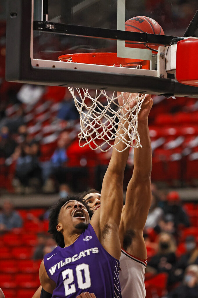 Abilene Christian's Coryon Mason (20) tips in a rebound during the second half of the team's NCAA college basketball game against Texas Tech, Wednesday, Dec. 9, 2020, in Lubbock, Texas. (AP Photo/Brad Tollefson)