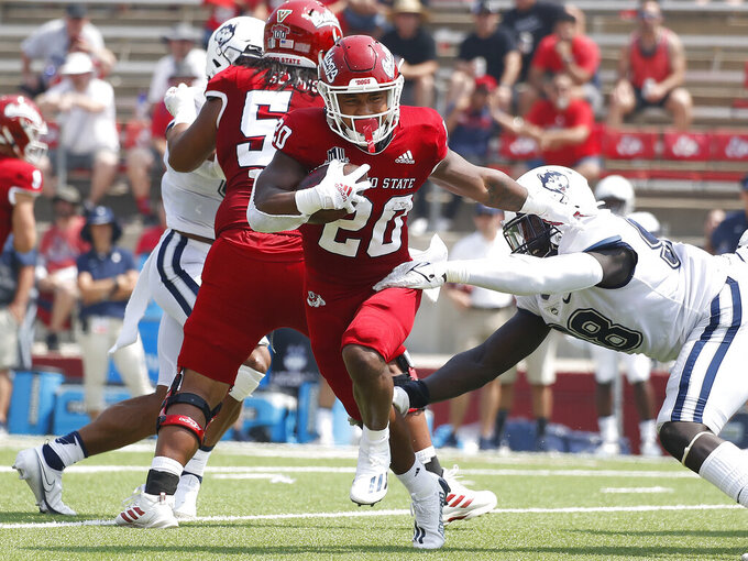 Fresno State running back Ronnie Rivers (20) runs past Connecticut defenders during the first half of an NCAA college football game in Fresno, Calif., Saturday, Aug. 28, 2021. (AP Photo/Gary Kazanjian)