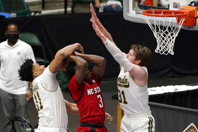 Colorado State forward Dischon Thomas (11) and forward Adam Thistlewood (31) defend against a shot attempt by North Carolina State guard Cam Hayes (3) during the first half of an NCAA college basketball game in the quarterfinals of the NIT, Thursday, March 25, 2021, in Frisco, Texas. (AP Photo/Tony Gutierrez)