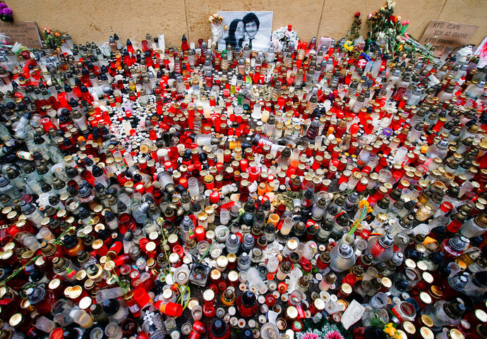 FILE- In this Friday, March 16, 2018 file photo candles are placed in memory of slain journalist Jan Kuciak and his fiancee Martina Kusnirova during a rally in Bratislava, Slovakia. On Monday, Oct. 21, 2019, Slovakia's prosecutors have indicted four suspects for the slaying of an investigative reporter and his fiancee, a case that brought down the Slovak government. (AP Photo/Darko Vojinovic, File)