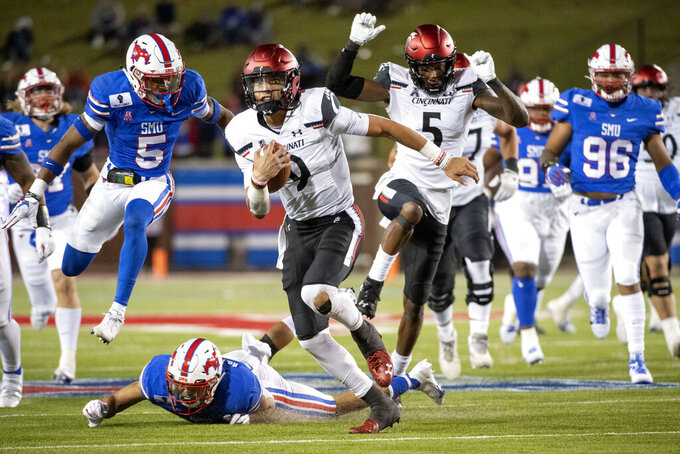 Cincinnati quarterback Desmond Ridder (9) runs away from SMU safety Roderick Roberson, Jr., on ground, and cornerback Ar'mani Johnson (5) on a touchdown run during the second half of an NCAA college football game Saturday, Oct. 24, 2020, in Dallas. (AP Photo/Jeffrey McWhorter)