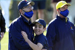 Lucas Bernstein, center, gets a hug from his dad, Michael, after winning his age group at the Drive Chip & Putt National Finals at Augusta National Golf Club, Sunday, April 4, 2021, in Augusta, Ga. (AP Photo/David J. Phillip)