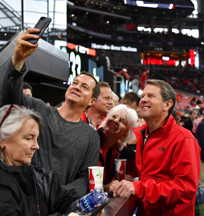 Georgia Governor-elect Brian Kemp, right, has his photo made by a fan ahead of the first half of the Southeastern Conference championship NCAA college football game between Georgia and Alabama, Saturday, Dec. 1, 2018, in Atlanta. (AP Photo/John Amis)