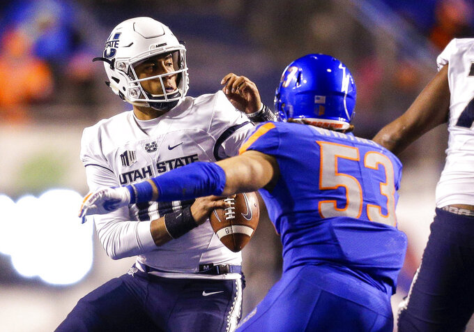 Utah State quarterback Jordan Love (10) tries to avoid the pressure brought by Boise State linebacker Sam Whitney (53) in the second of an NCAA college football game, Saturday, Nov. 24, 2018, in Boise, Idaho. Boise State won 33-24. (AP Photo/Steve Conner)