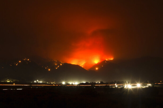 The Holy Fire burns in the distance above I-15 on Thursday night, Aug. 9, 2018 in Temescal Valley, Calif.  More than a thousand firefighters battled to keep a raging Southern California forest fire from reaching foothill neighborhoods Friday before the expected return of blustery winds that drove the flames to new ferocity a day earlier. (AP Photo/Patrick Record)