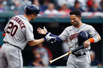 Houston Astros' Jose Altuve (27) celebrates with Chas McCormick (20) after scoring on a double by Carlos Correa off Cleveland Indians' Sam Hentges during the third inning of a baseball game, Friday, July 2, 2021, in Cleveland. (AP Photo/Ron Schwane)