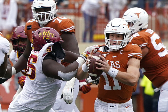 Texas quarterback Sam Ehlinger (11) is pressured by Iowa State defensive lineman Latrell Bankston (56) during the second half of an NCAA college football game, Friday, Nov. 27, 2020, in Austin, Texas. (AP Photo/Eric Gay)