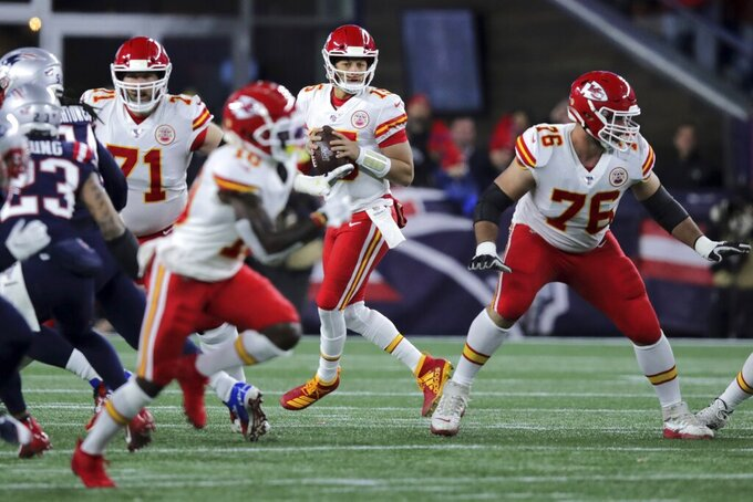 Kansas City Chiefs quarterback Patrick Mahomes, center, rolls out to pass against the New England Patriots in the first half of an NFL football game, Sunday, Dec. 8, 2019, in Foxborough, Mass. (AP Photo/Charles Krupa)