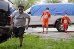 Victor Ochoa, 9, left, runs as his brothers watch him in front of their home in Chicago, Friday, May 22, 2020. Mariana Ochoa has three young boys, ages 9, 7, and 5, and Chicago Run's at-home fitness programs have become an essential part of the family's routine during the coronavirus pandemic. (AP Photo/Nam Y. Huh)