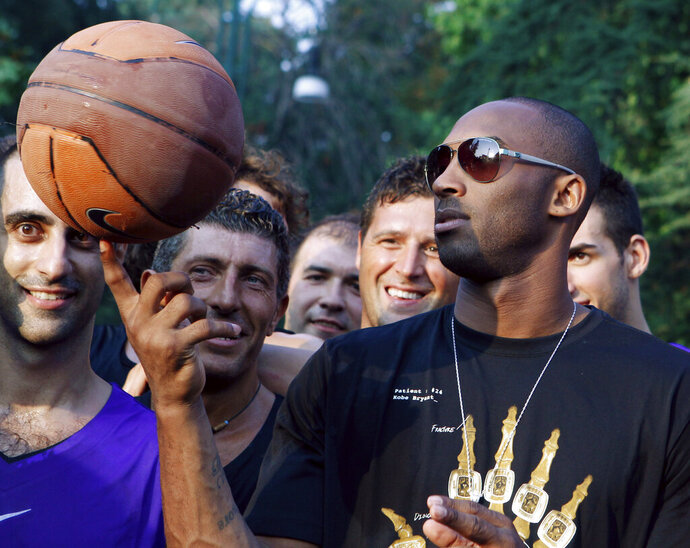 FILE - In this Sept. 28, 2011, file photo, U.S. basketball star Kobe Bryant plays with a ball during a sponsor's appearance in Milan, Italy. In Europe where Bryant grew up, the retired NBA star is being remembered for his