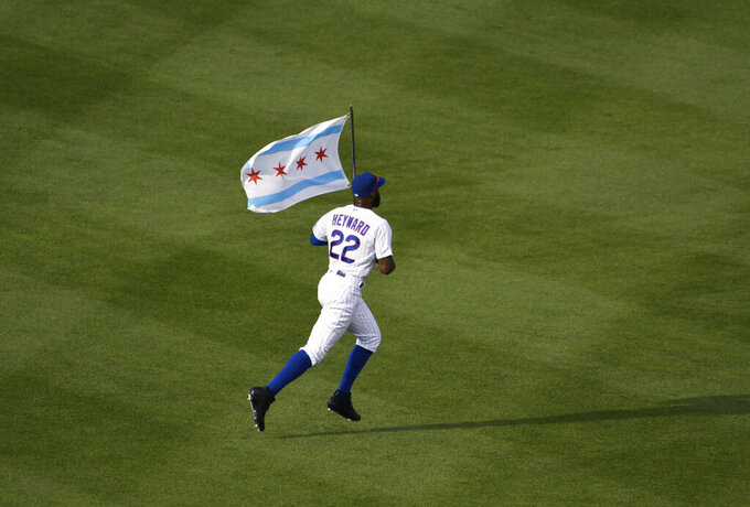 Chicago Cubs right fielder Jason Heyward takes the field with a flag of Chicago before an opening day baseball game against the Milwaukee Brewers, Friday, July, 24, 2020, in Chicago. (AP Photo/David Banks)