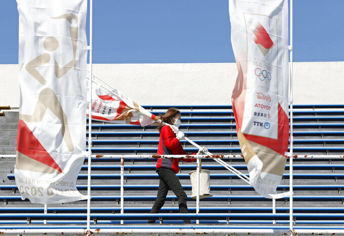 A worker carries flags in preparation for the Olympic torch relay, in Iwaki, Fukushima prefecture, northeastern Japan Tuesday, March 23, 2021. The torch relay opens on Thursday from the prefecture. (Fumine Tsutabayashi/Kyodo News via AP)