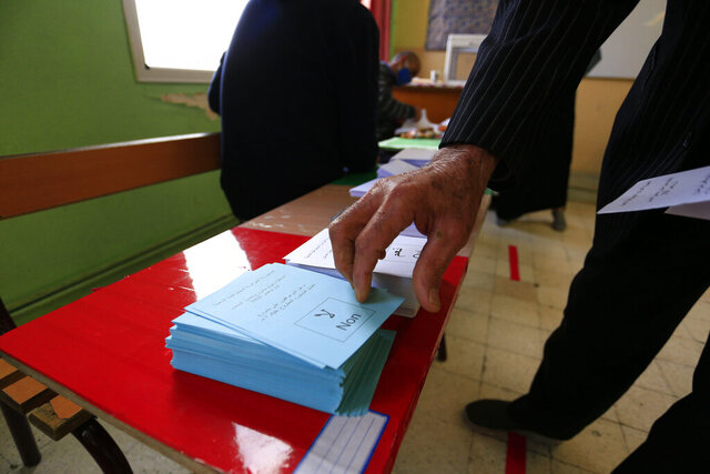 A man prepares to vote at a polling station during a vote for a revised constitution, in Algiers, Sunday, Nov. 1, 2020. Algerians are voting on whether to approve a revised constitution that imposes term limits and aims at answering demands from pro-democracy protesters who pushed out the president last year. (AP Photo/Toufik Doudou)