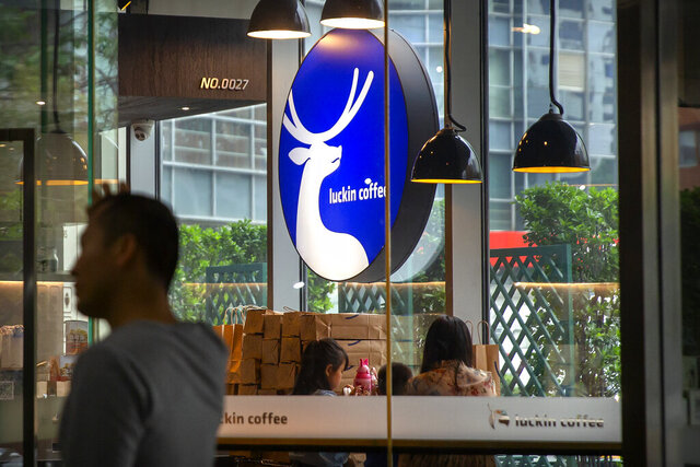 In this May 18, 2019, photo, customers sit at a Luckin Coffee outlet in a shopping mall in Beijing. The U.S. market watchdog says China's Luckin Coffee has agreed to pay a $180 million penalty to settle accounting fraud charges. The Securities and Exchange Commission charged the company with defrauding investors by misstating its revenue, expenses, and net operating loss to appear to have been more profitable and growing faster than it actually was, and to meet the company's earnings estimates. (AP Photo/Mark Schiefelbein)