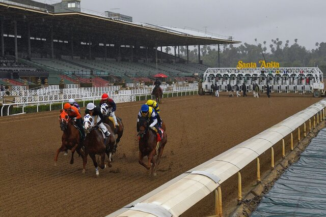 FILE - In this March 14, 2020, file photo, horses run in the fourth race at Santa Anita Park in front of empty stands in Arcadia, Calif. Opening day of Santa Anita's fall season will be pushed back a week until Sept. 25 because of poor air quality from a wildfire burning near the Southern California racetrack. (AP Photo/Mark J. Terrill, File)