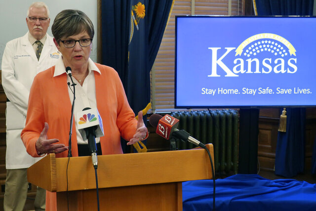 Kansas Gov. Laura Kelly answers questions about the coronavirus pandemic as Dr. Lee Norman, the state's health secretary, watches during a news conference, Friday, June 5, 2020, at the Statehouse in Topeka, Kan. Kelly says her administration will consider using federal coronavirus relief funds to start a program to help people struggling to pay their rent or home mortgages. (AP Photo/John Hanna)