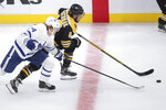 Boston Bruins right wing David Pastrnak (88) chases the puck next to Toronto Maple Leafs right wing Kasperi Kapanen, left, during the first period of an NHL hockey game in Boston, Tuesday, Oct. 22, 2019. (AP Photo/Charles Krupa)