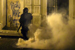 A member of the riot control units patrol the street during clashes in San Juan, Puerto Rico, Monday, July 22, 2019.  Protesters are demanding Gov. Ricardo Rossello step down following the leak of an offensive, obscenity-laden online chat between him and his advisers that triggered the crisis.    (AP Photo /Carlos Giusti)