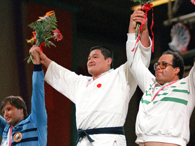 Japan's Yasuhiro Yamashita, center, celebrates winning gold medal at a judo match of the 1984 Los Angeles Olympics in Los Angeles on Aug. 11, 1984. Yamashita overcame a leg injury to win a gold medal at the Olympics, limping to the awards-ceremony podium. He preaches judo's appeal comes from building one's body and character. (Kyodo News via AP)