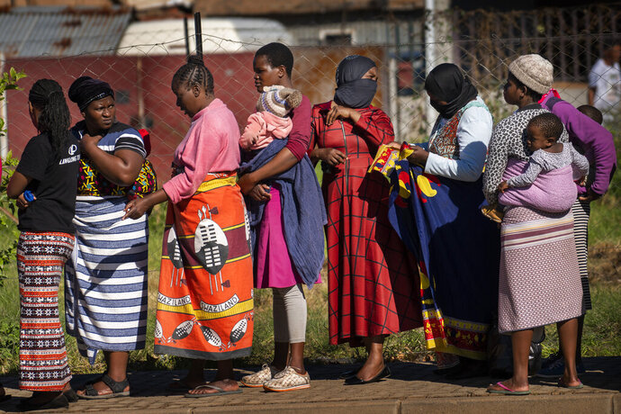 FILE- In this file photo taken Thursday, April 30, 2020, Women carrying their children lineup to receive vegetables from the Jan Hofmeyer community services in the Vrededorp neighborhood of Johannesburg. South Africa is struggling to balance its fight against the coronavirus with its dire need to resume economic activity. The country with the Africa's most developed economy also has its highest number of infections — more than 19,000.  (AP Photo/Jerome Delay, file)