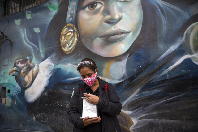 Maritza Lujan, backdropped by a mural painted on a warehouse featuring an Inca princess and condor, caresses the marble urn that contains the cremated remains of her father after a funeral home service delivered them to her at a designated meeting place near her home, in Lima, Peru, Monday, June 22, 2020. Her 67-year-old father, Hugo Lujan, died from symptoms related to COVID-19. (AP Photo/Rodrigo Abd)