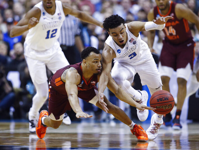 Duke guard Tre Jones (3) loses the ball as he runs into Virginia Tech guard Justin Robinson during the first half of an NCAA men's college basketball tournament East Region semifinal in Washington, Friday, March 29, 2019. (AP Photo/Patrick Semansky)