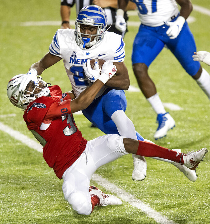 Memphis running back Asa Martin (28) tries to run over Florida Atlantic safety Armani-Eli Adams (30) during the Montgomery Bowl NCAA college football game in Montgomery, Ala., Wednesday, Dec. 23, 2020. (Mickey Welsh/The Montgomery Advertiser via AP)