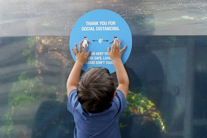 A young child reaches up to touch a social distancing sign on the glass of an outdoor seal exhibit at the New England Aquarium, Wednesday, May 26, 2021, in Boston. The nation's tourist destinations are facing a severe worker shortage just as they try to rebound from a year lost to the coronavirus pandemic. (AP Photo/Mary Schwalm)