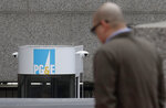 File - In this Jan. 29, 2019, file photo, a man crosses the street in front of a Pacific Gas and Electric building in San Francisco. An effort to block Pacific Gas and Electric's path out of bankruptcy kicked off the trial Wednesday, May 27, 2020, on the plan in bankruptcy court as critics of the utility questioned whether the overwhelming vote in favor of the plan by wildfire victims was tainted by conflicts of interest and shoddy counting. PG&E's plan won support last week in a landslide, with victims overwhelmingly backing PG&E's $58 billion proposal to emerge from bankruptcy after 18 months.  (AP Photo/Jeff Chiu, File)