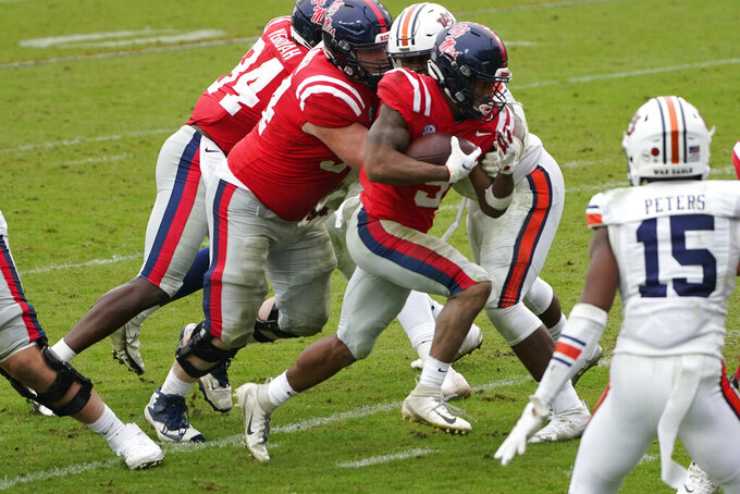 Following his blockers Mississippi running back Jerrion Ealy (9) runs past Auburn defenders for a five-yard touchdown run during the first half of an NCAA college football game in Oxford, Miss., Saturday Oct. 24, 2020. Auburn won 35-28. (AP Photo/Rogelio V. Solis)