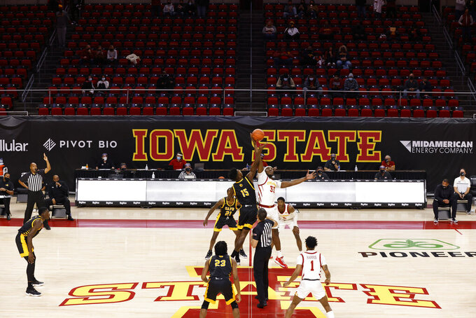 Arkansas-Pine Bluff forward Alvin Stredic and Iowa State forward Solomon Young leap for the tip-off during the first half of an NCAA college basketball game with few people in the stands, Sunday, Nov. 29, 2020, in Ames, Iowa. (AP Photo/Matthew Putney)