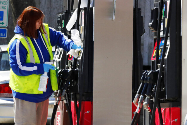 FILE - In this March 31, 2020 file photo, a worker cleans and sanitizes a pump at the Speedway gas station in Concord, N.H. U.S. consumer prices rose 0.4% in August as energy prices moderated after big gains in the previous two months.(AP Photo/Charles Krupa, File)