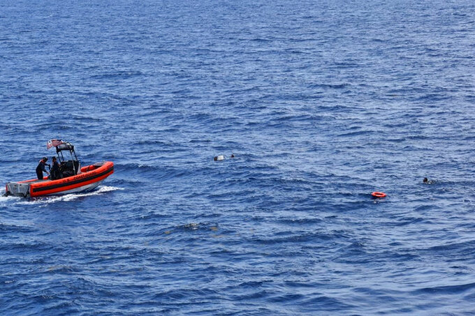 In this image released by the U.S. Coast Guard, a Coast Guard crew rescues eight people from the water approximately 16 miles south of Key West, Florida, on Thursday, May 27, 2021. A search for 10 Cubans missing from a boat capsize continued Friday, a day after the U.S. Coast Guard rescued other passengers and pulled two bodies from the water. (U.S. Coast Guard via AP)