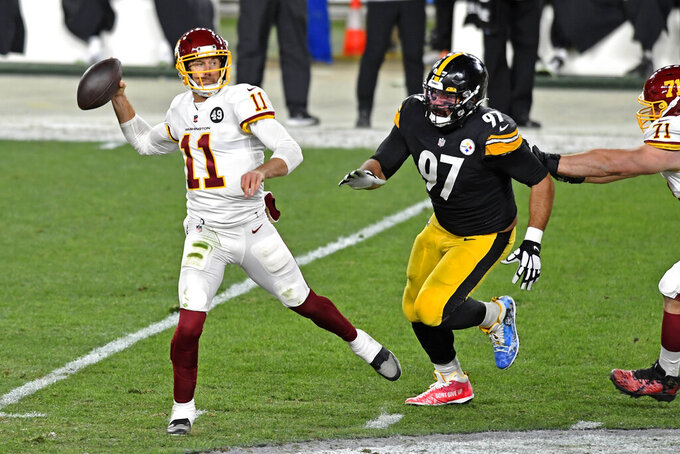 Washington Football Team quarterback Alex Smith (11) prepares to pass under pressure from Pittsburgh Steelers defensive end Cameron Heyward (97) during the first half of an NFL football game in Pittsburgh, Monday, Dec. 7, 2020. (AP Photo/Barry Reeger)
