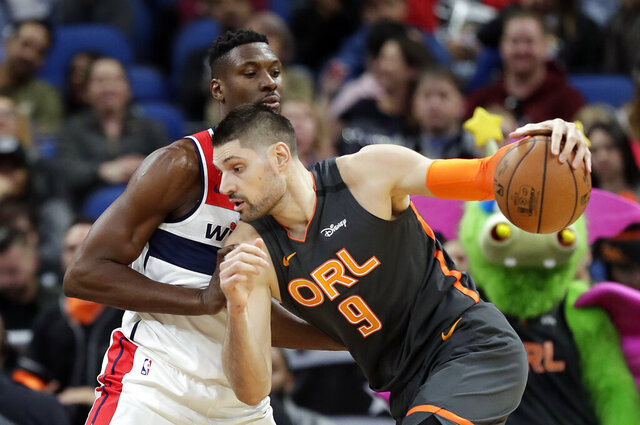 Orlando Magic center Nikola Vucevic (9) drives to the basket against Washington Wizards center Ian Mahinmi during the first half of an NBA basketball game Wednesday, Jan. 8, 2020, in Orlando, Fla. (AP Photo/John Raoux)