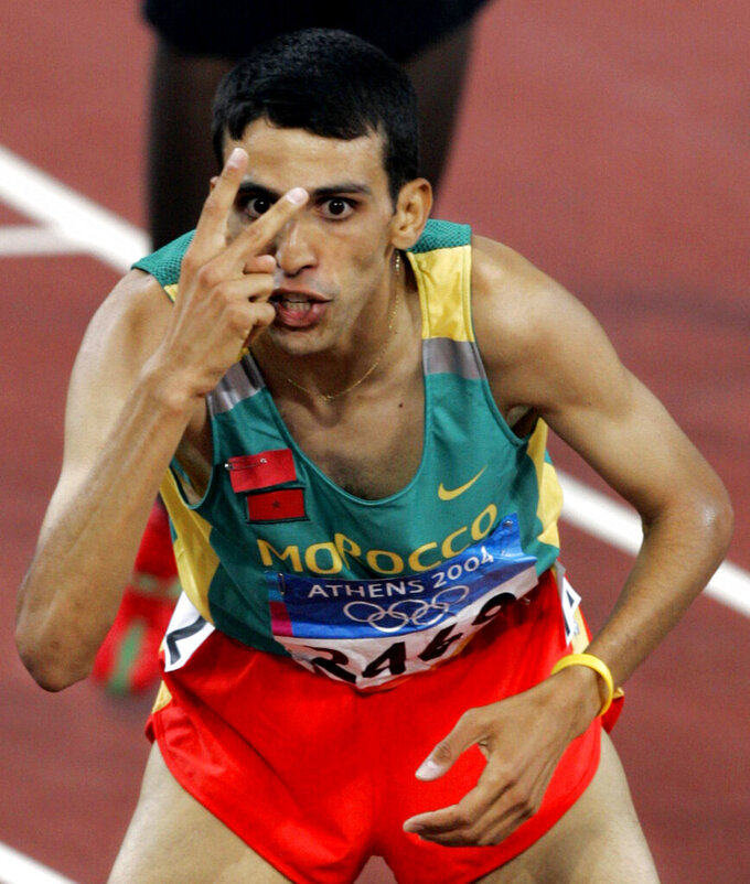 FILE - In this Aug. 28, 2004, file photo, Morocco's Hicham El Guerrouj celebrates after winning the gold medal in the 5000-meter final, his second gold medal of the games, at the Olympic Stadium during the 2004 Olympic Games in Athens. El Guerrouj also won a gold medal in the 1500-meters. (AP Photo/Rusty Kennedy, File)