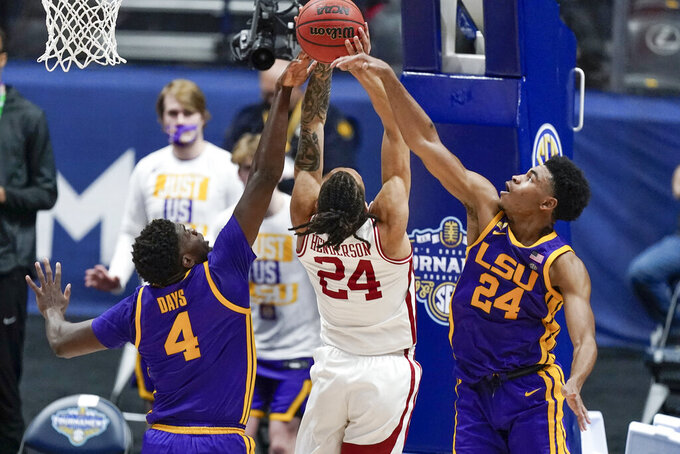 Arkansas' Ethan Henderson (24) reaches for a rebound with LSU's Darius Days (4) and Cameron Thomas (24) in the first half of an NCAA college basketball game in the Southeastern Conference Tournament Saturday, March 13, 2021, in Nashville, Tenn. (AP Photo/Mark Humphrey)