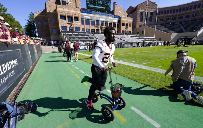 Injured Minnesota running back Mohamed Ibrahim looks on as teammates warm up before an NCAA college football game against Colorado, Saturday, Sept. 18, 2021, in Boulder, Colo. (AP Photo/David Zalubowski)