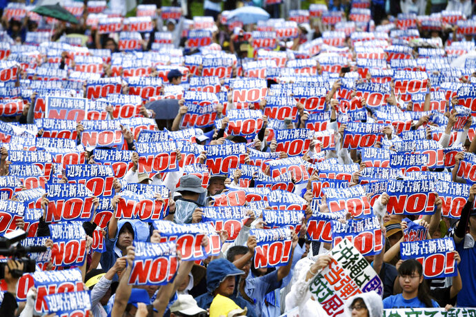 Protesters display signs against a planned U.S military base relocation during a rally in Naha, Okinawa prefecture, on the southern Japanese island Saturday, Aug. 11, 2018. (Koji Harada/Kyodo News via AP)