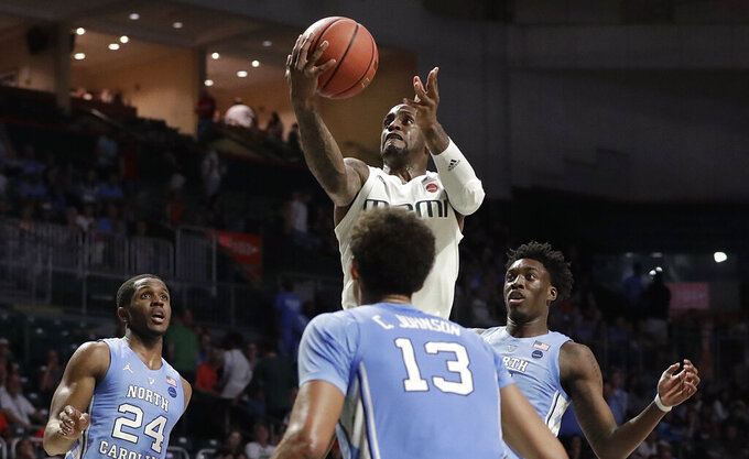 Miami guard Zach Johnson shoots against North Carolina guards Kenny Williams, left, and Cameron Johnson, center, and forward Nassir Little during the second half of an NCAA college basketball game on Saturday, Jan. 19, 2019, in Coral Gables, Fla. (AP Photo/Brynn Anderson)
