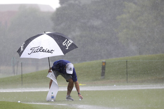 Equipment is picked up off the practice green as rain falls at the World Golf Championship-FedEx St. Jude Invitational Wednesday, July 29, 2020, in Memphis, Tenn. (AP Photo/Mark Humphrey)
