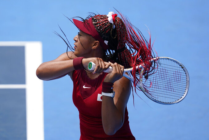 Naomi Osaka, of Japan, serves to Viktorija Golubic, of Switzerland, during second round of the tennis competition at the 2020 Summer Olympics, Monday, July 26, 2021, in Tokyo, Japan. (AP Photo/Patrick Semansky)