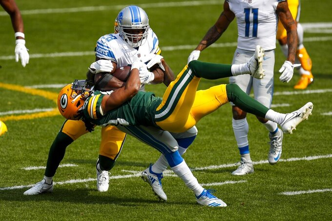 Green Bay Packers' Kevin King and Chandon Sullivan stop Detroit Lions' Adrian Peterson during the first half of an NFL football game Sunday, Sept. 20, 2020, in Green Bay, Wis. (AP Photo/Matt Ludtke)