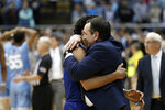 Duke guard Tre Jones hugs head coach Mike Krzyzewski following and overtime victory in an NCAA college basketball game against North Carolina in Chapel Hill, N.C., Saturday, Feb. 8, 2020. (AP Photo/Gerry Broome)