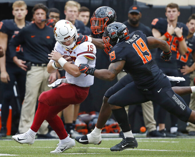 Oklahoma State linebacker Calvin Bundage (1), rear, pulls on the helmet of Iowa State quarterback Brock Purdy (15) during a tackle and is called for a penalty in the second half of an NCAA college football game in Stillwater, Okla., Saturday, Oct. 6, 2018. Oklahoma State linebacker Justin Phillips (19) is at right. (AP Photo/Sue Ogrocki)