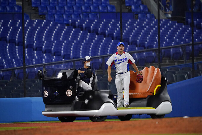 South Korea's Woosuk Go arrives to pitch in the seventh inning of a baseball game against the Dominican Republic at the 2020 Summer Olympics, Sunday, Aug. 1, 2021, in Yokohama, Japan. (AP Photo/Sue Ogrocki)